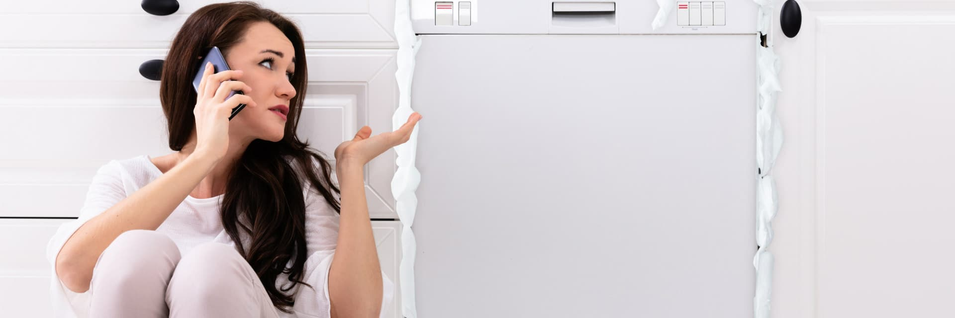 woman on the phone sitting in front of a dishwasher leaking suds