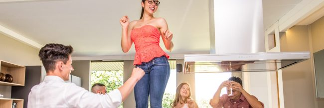 girl dancing on a table with people around