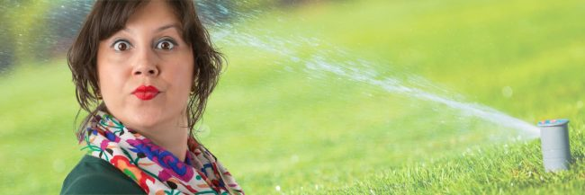 snotty woman with sprinkler aiming toward her
