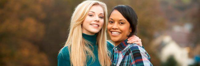 blonde girl and dark haired girl hugging
