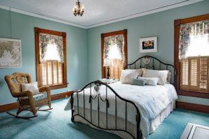 vintage bedroom with iron bed and teal carpet and whicker rocker