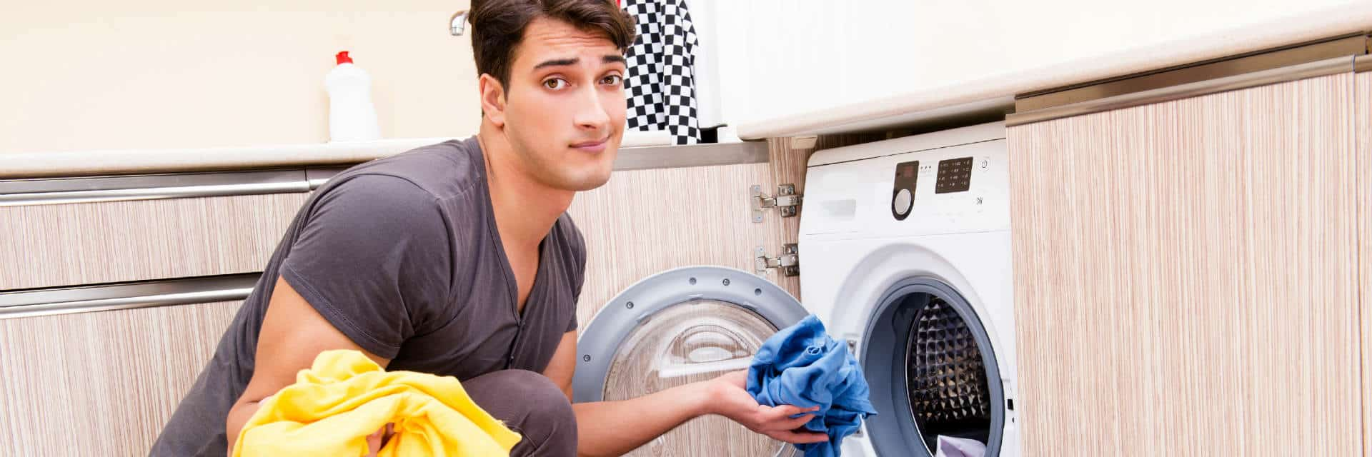 young man putting laundry in a washing machine
