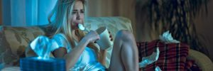 woman sitting on a couch eating ice cream gaining covid 15