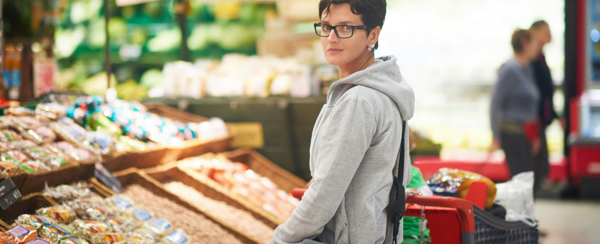 woman standing in front of produce at grocery store