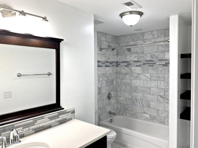 Marble tub surround with dark wood shelving