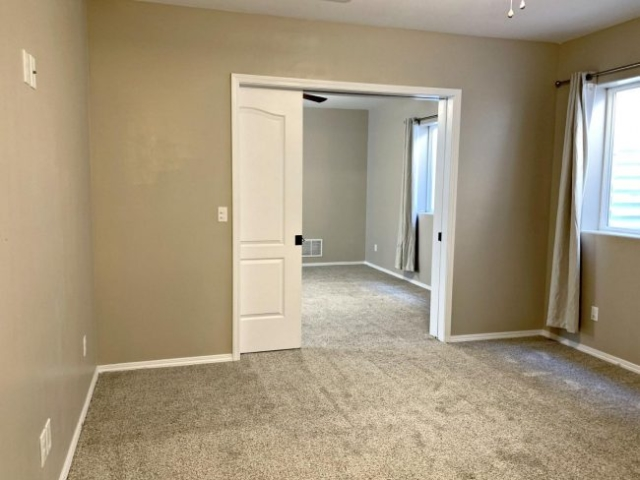 basement master bedroom with pocket doors toward family room