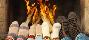 four pair of socked feet at fireplace