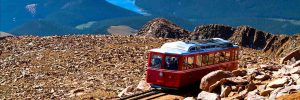 Pikes Peak Cog Railway car traveling doen from top of Pikes Peak mountain top in Colorado on sunny summer morning with mountains and lake in distance