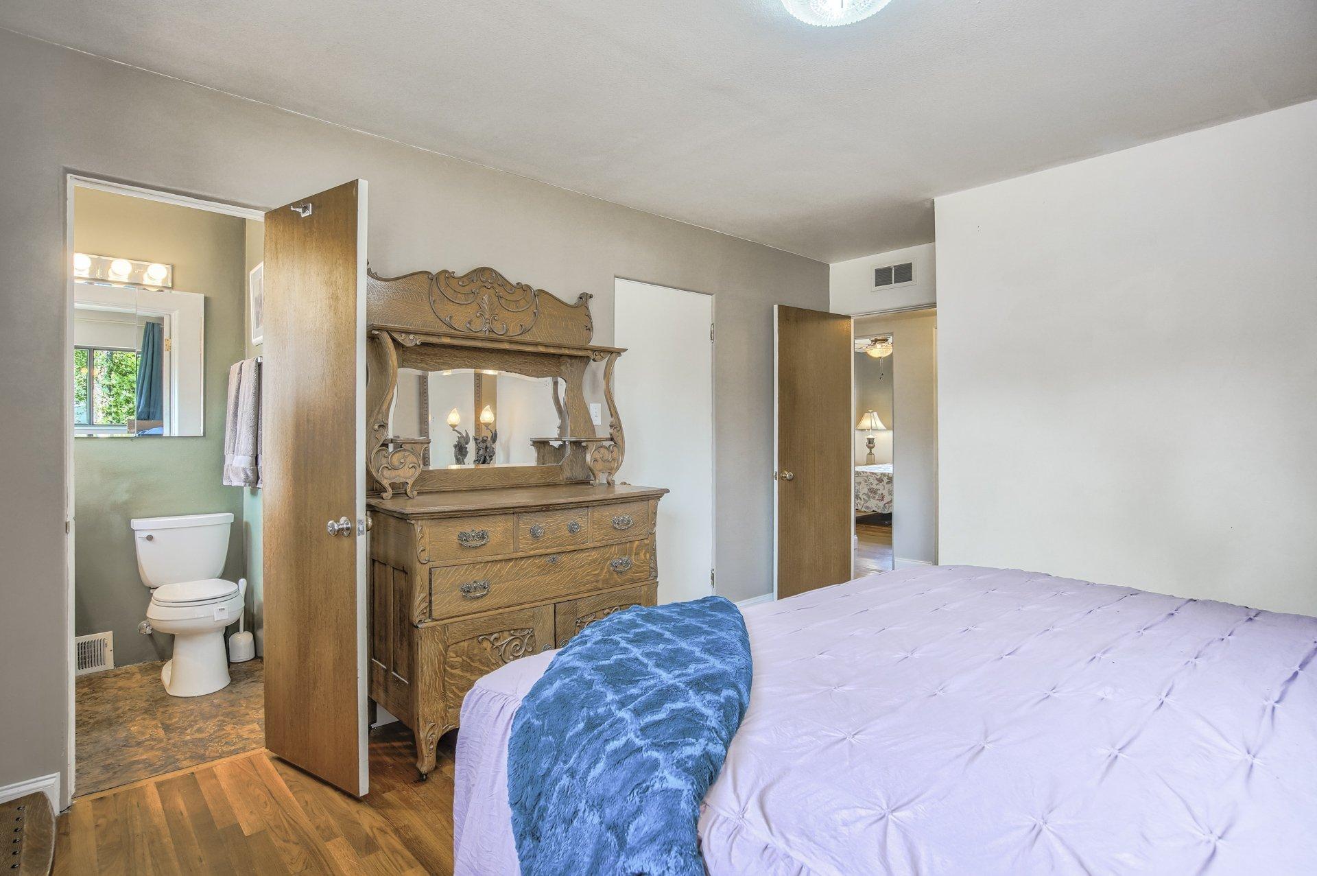 Bed and dresser looking toward bathroom