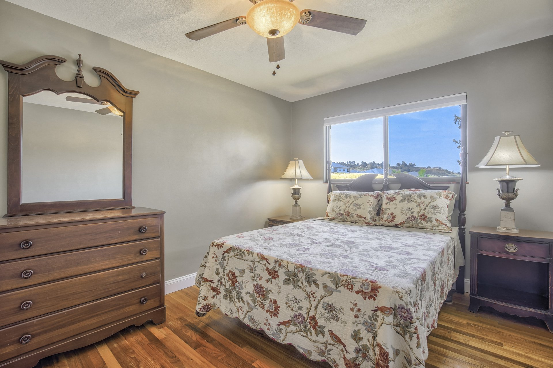 bed and dresser in room with wood floors
