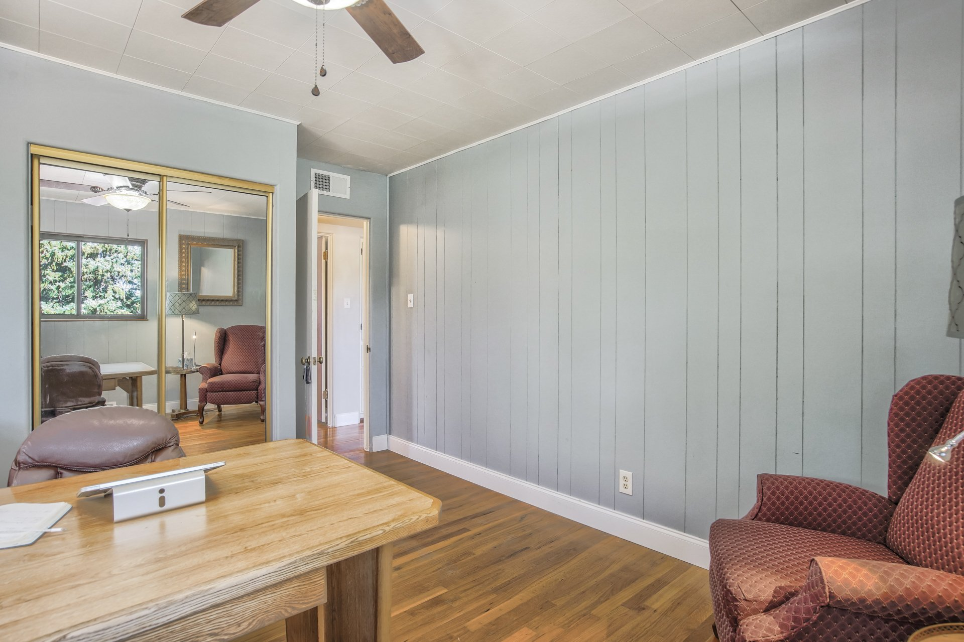 desk and chair in room with oak floors