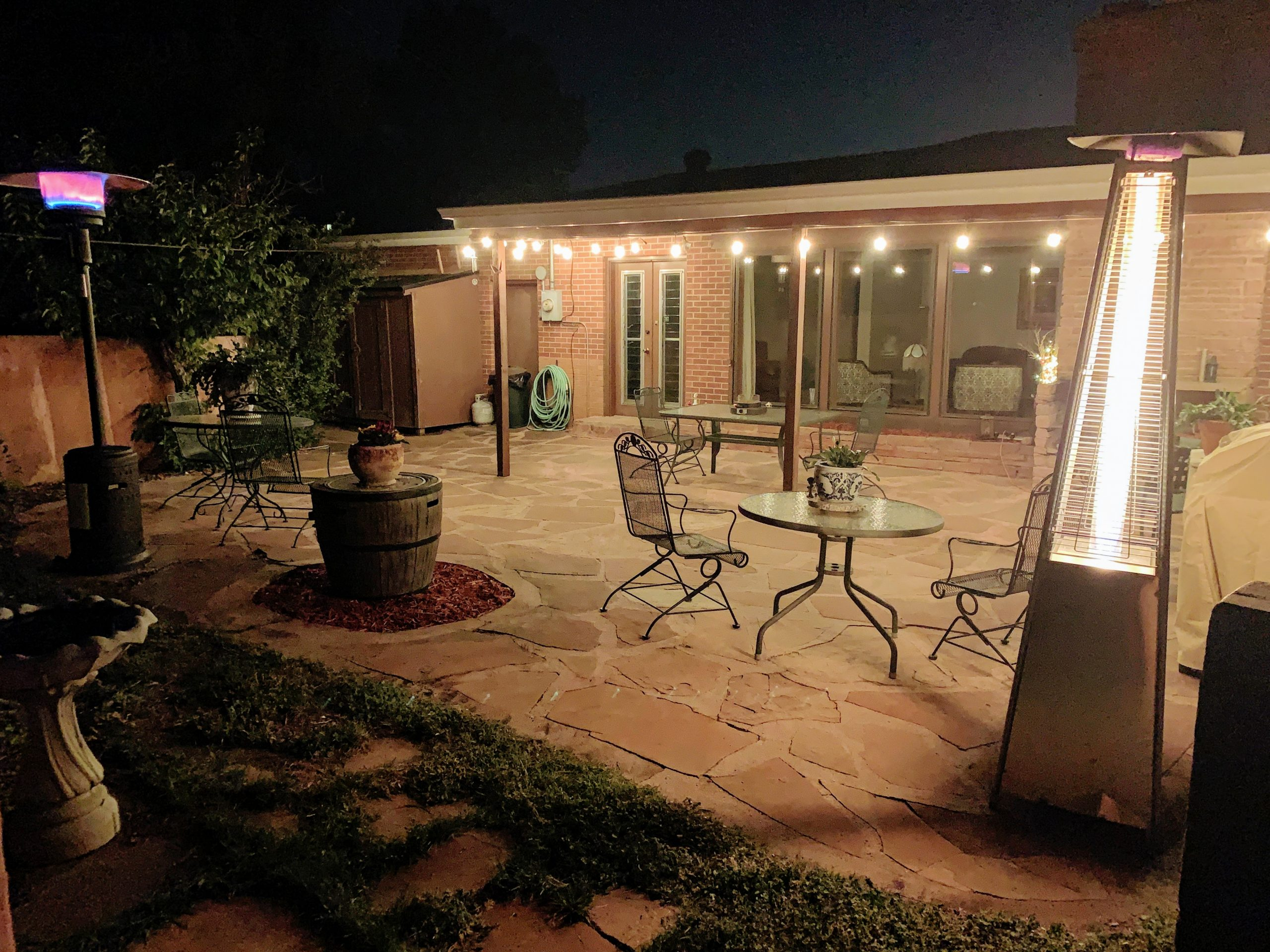 Two heaters burning on patio at nighttime